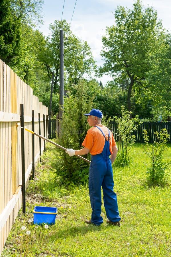 Tuinman in blauwe eenvormige verven nieuwe houten omheining royalty-vrije stock foto