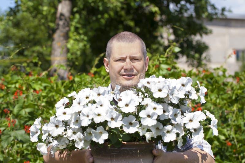 Tuinman met bloemen in de tuin stock foto