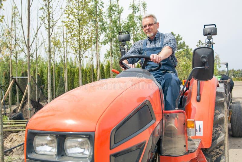 Tuinmanritten op de tractor bij tuinopslag stock foto