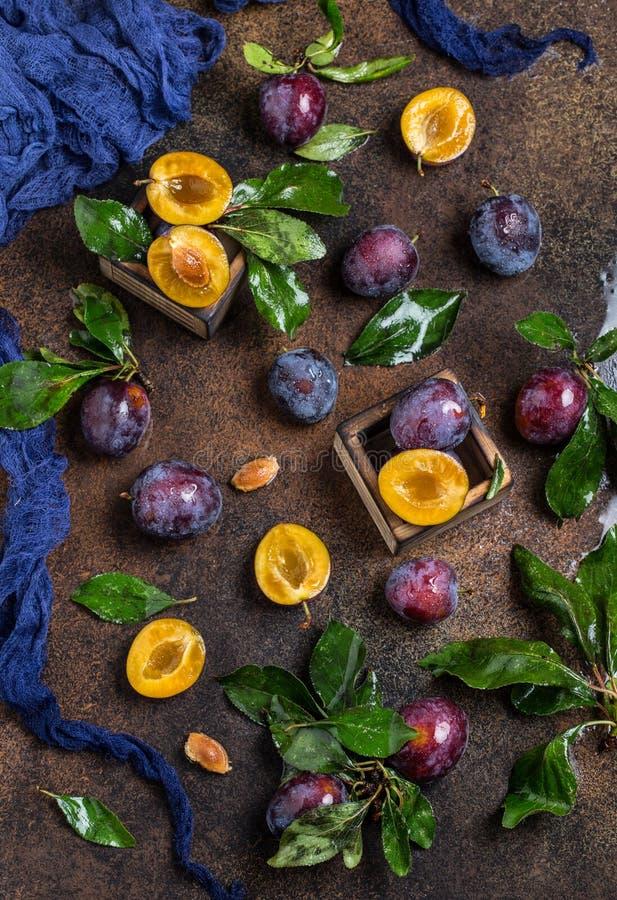 Tuinpruimen op lijst Sluit omhoog van verse pruimen met bladeren De herfstoogst van pruimen royalty-vrije stock fotografie