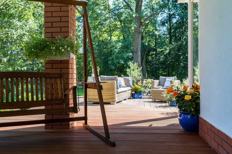 Tuinschommeling en een comfortabel terras stock fotografie