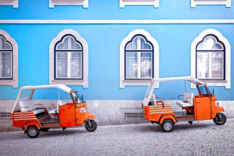 Tuk在蓝色门面大厦前面的tuk车在里斯本,葡萄牙 库存照片