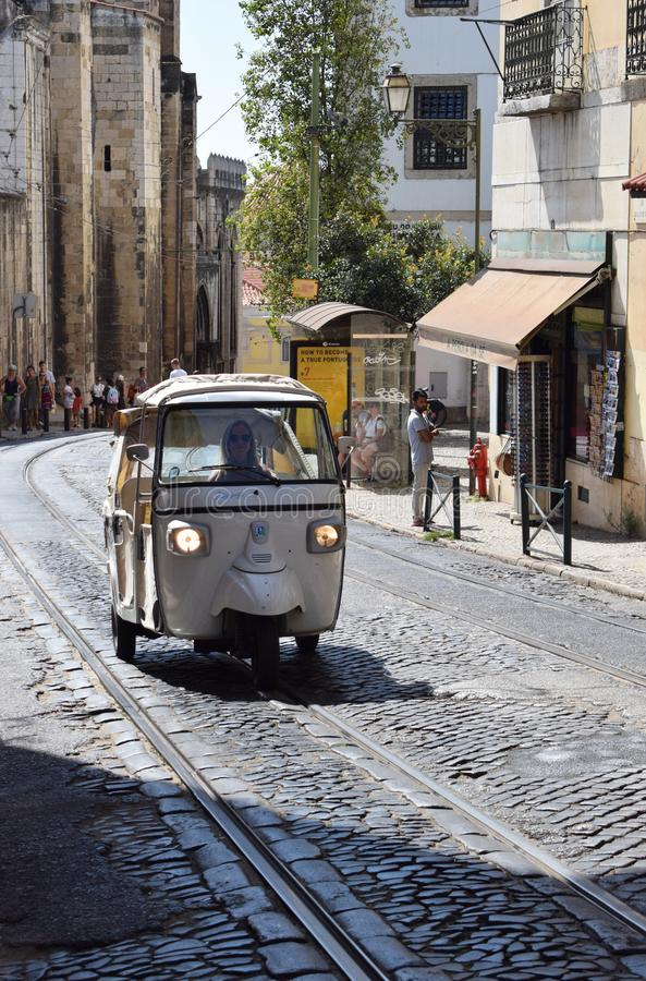 A tuk tuk in Alfama Lisbon Portugal. A tuk tuk being driven up the steep cobbled streets of Lisbon`s old city known as Alfama. The tukttuks in Lisbon are popular stock photo