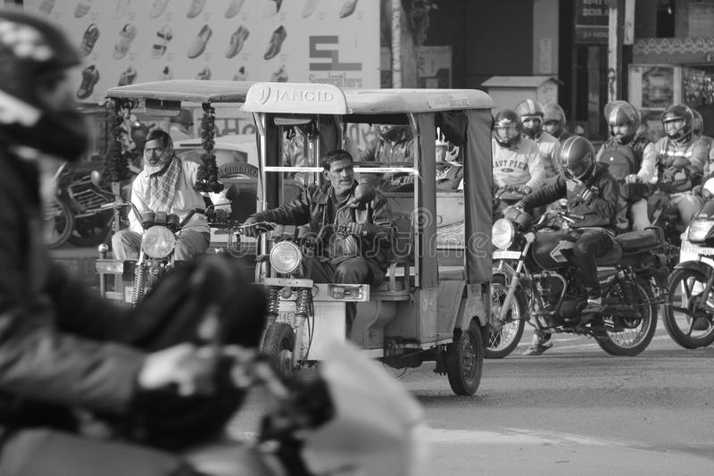 Tuk tuk car in busy traffic street in India. Tuk Tuk, also known as auto rickshaw in India is driven by old drive in the main streets of India. This is a very stock image