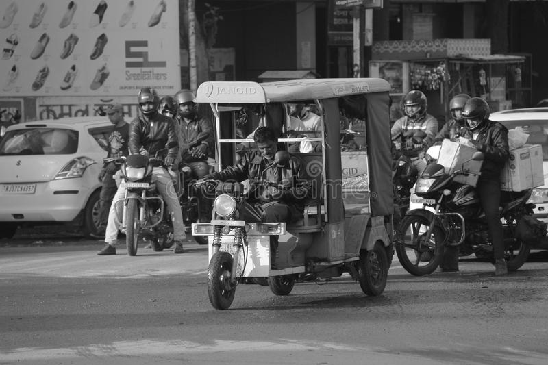 Tuk tuk car in busy traffic street in India. Tuk Tuk, also known as auto rickshaw in India is driven by old drive in the main streets of India. This is a very stock images
