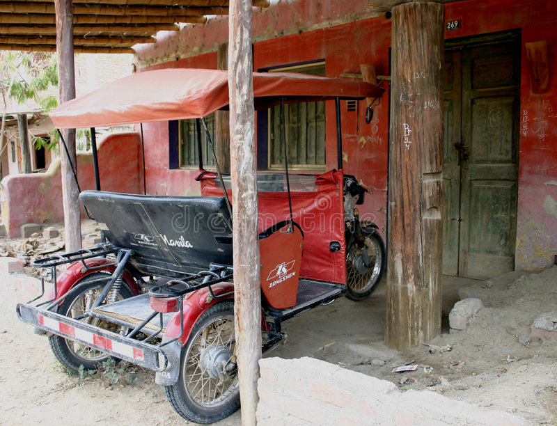 Tuk tuk parked in village house royalty free stock photo