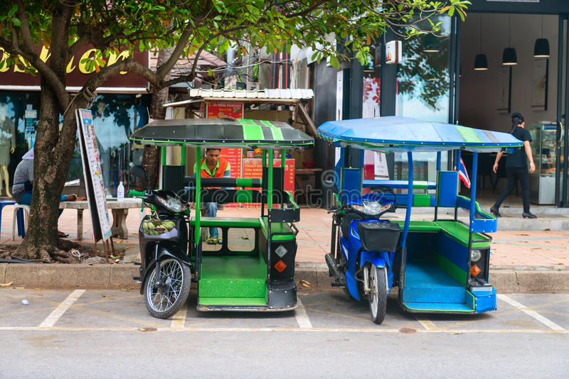 Tuk tuk taxis parked under a tree royalty free stock photo
