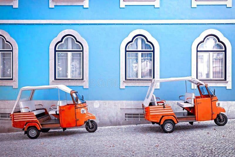 Tuk tukmedel som är främst av blå fasadbyggnad i Lissabonet, Portugal arkivfoto