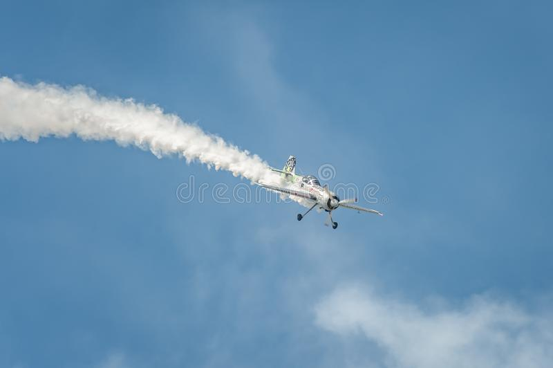Airplane performing at airshow and leaves behind a smokes in the sky royalty free stock photography