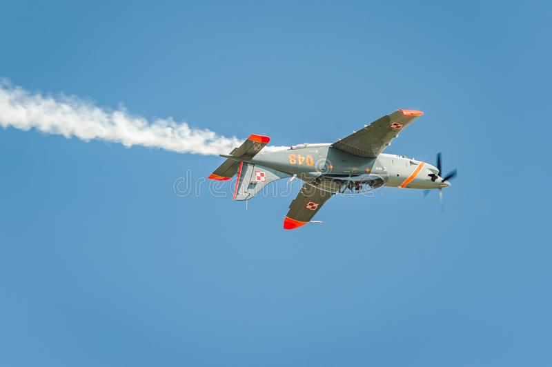 Airplane performing at airshow and leaves behind a smokes in the sky. Upside-down flight royalty free stock photos