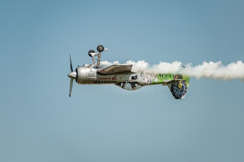 Irplane performing at airshow and leaves behind a smokes in the sky. Upside-down flight stock image