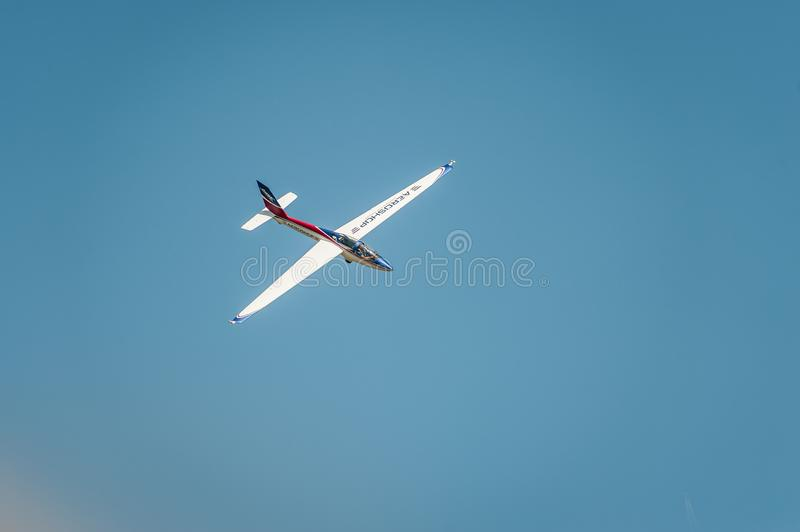 Aircraft flies and shows a performance at the airshow in the clear blue sky stock image