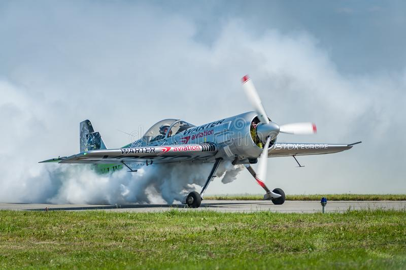 Airplane performing at airshow and shows a stunt on the runway royalty free stock photo