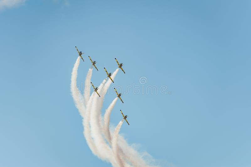 Baltic Bees team performs flight at air show and leaves behind a smokes in the sky royalty free stock photo