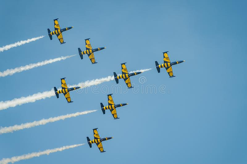 Baltic Bees team performs flight at air show and leaves behind a smokes in the sky royalty free stock photography
