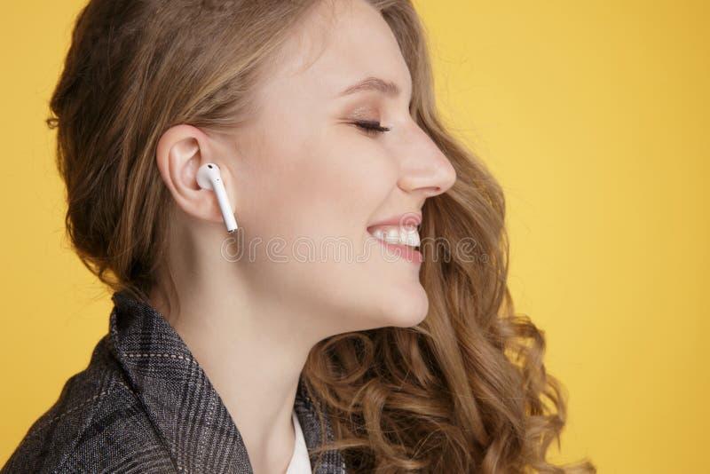 Tula, Rússia - 24 DE JANEIRO DE 2019: Rádio de escuta de Apple AirPods da música da mulher feliz fotografia de stock