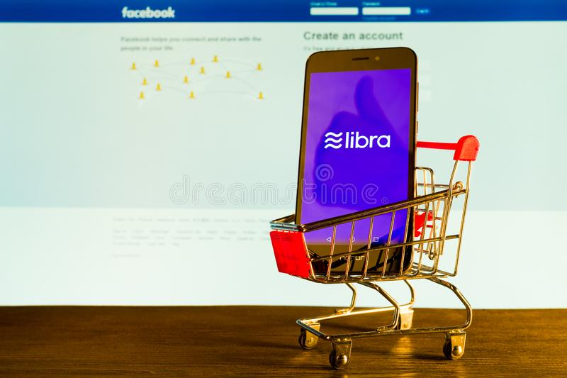 Tula, Rússia - 4 de julho de 2019: Conceito do blockchain da moeda da Libra com o smartphone no carrinho de compras ao lado do mo fotos de stock