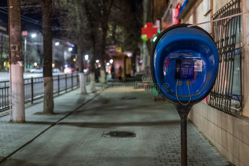 TULA, RUSSIA - APRIL 22, 2017: blue payphone post at night city sidewalk with selective focus.  stock photo