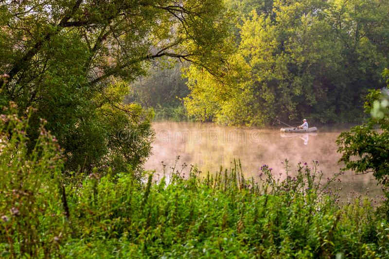 TULA, RUSSIA - AUGUST 12, 2013: A man fishing on river at inflatable boat at foggy summer morning under green foliage royalty free stock image