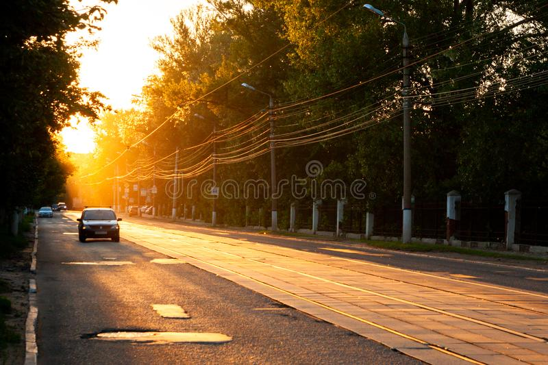 TULA, RUSSIA - JUNE 6, 2013: Car on city street under golden sun backlight. Air glowing bright stock photo