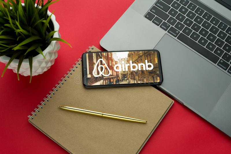 Tula, Russia, november 26, 2019: Airbnb logo on the smartphone screen is placed on the Apple macbook keyboard on red desk. Background.- Image royalty free stock image