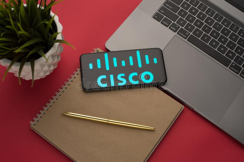 Tula, Russia, november 26, 2019: Cisco logo on the smartphone screen is placed on the Apple macbook keyboard on red desk. Background.- Image, flatlay, top, view stock photos