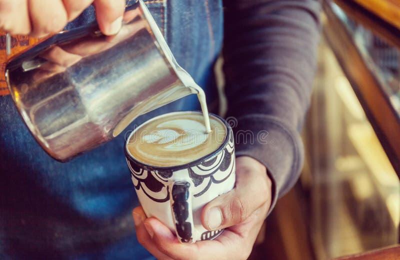 Tulip?n de colada del foame del latte del barista profesional sobre el caf?, el caf? express y crear un capuchino perfecto imagen de archivo