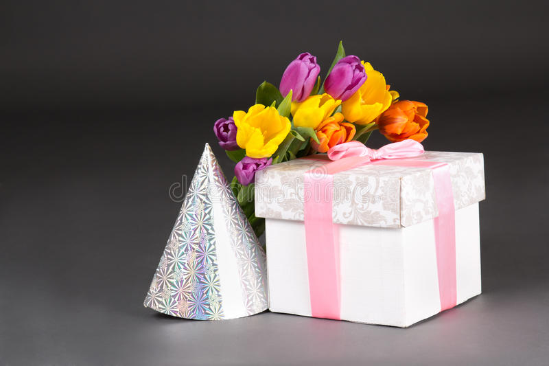 Tulip bouquet, gift box and birtday hat. On grey royalty free stock image