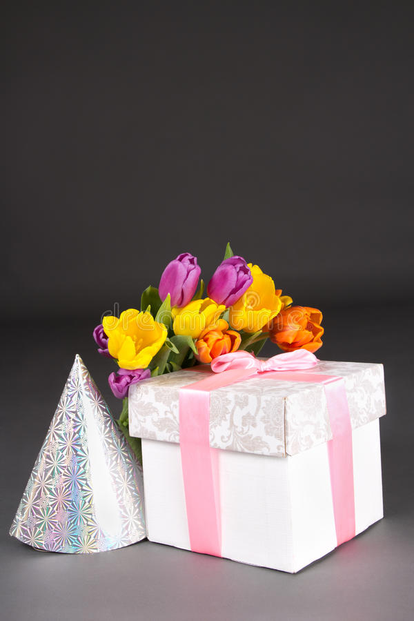 Tulip bouquet with gift box and birtday hat. On grey royalty free stock photography