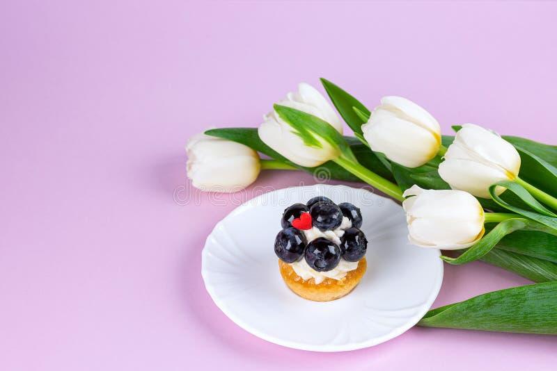 Tulip bouquet and mignon cake closeup royalty free stock photo