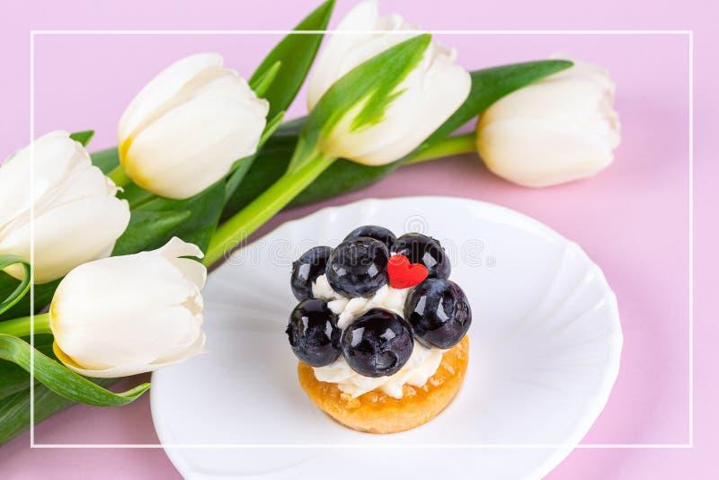 Tulip bouquet and mignon cake. Frame stock photos