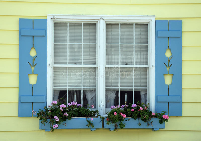 Tulip Cottage Window. Cute cottage with tulips carved into shutters and flower boxes in front of the window