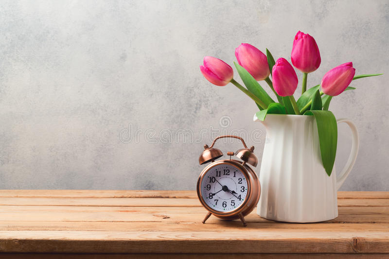 Tulip flowers bouquet and retro alarm clock stock photo