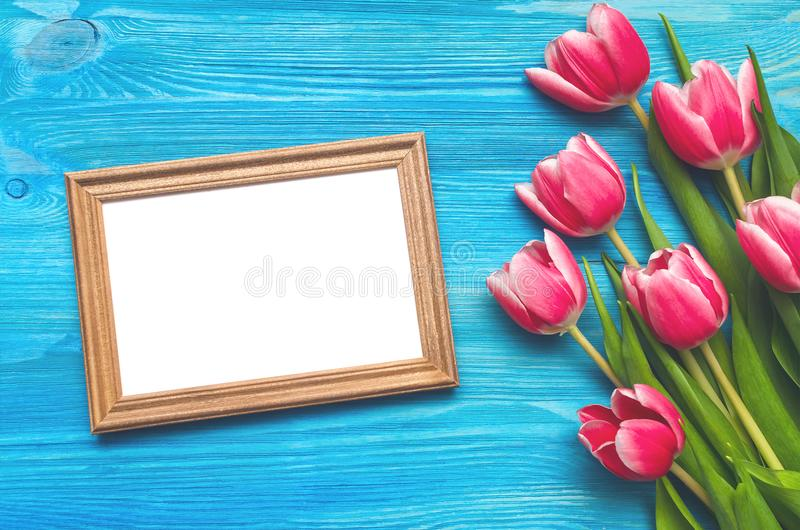 Tulip flowers and empty photo frame on wooden background with copy space. Woman day concept. Romantic background. stock photos