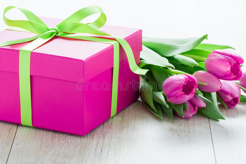 Tulip Flowers and Giftbox on rustic table for March 8, International Womens Day, Birthday , Valentines Day or Mothers day - Close stock image
