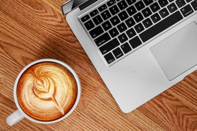 Tulip Latte Art and Laptop on Oak Wood Surface royalty free stock photo