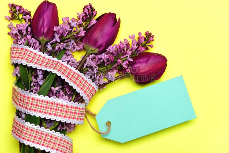 Tulip and lilac flowers with ribbon and cyan note label. Tulip and lilac flowers with plaid ribbon and cyan note label on yellow background, top view and copy stock photography