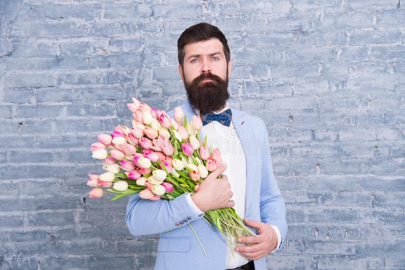 Tulip. Spring gift. Bearded man hipster with tulip flowers. Bearded man with tulip bouquet. Womens day. Flower for March. 8. Love date. international holiday stock photo