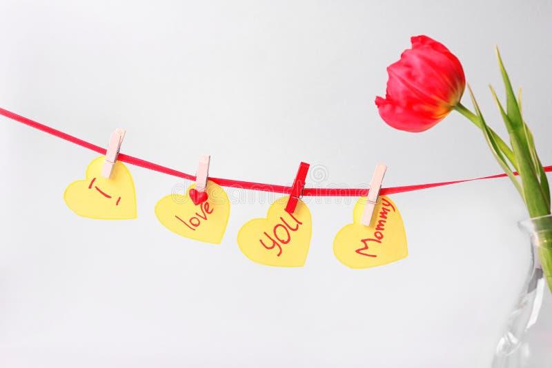 Tulipa bonita e festão feitas das etiquetas com a MAMÃ das palavras EU TE AMO no fundo branco fotos de stock