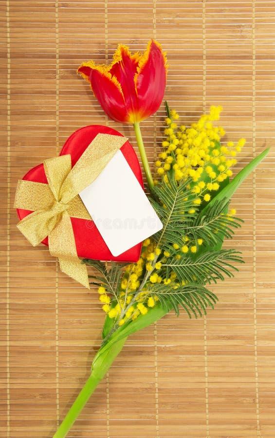 Tulipan, mimozy, prezent w serce formie i karta, fotografia stock