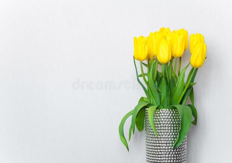 Tulipanes amarillos brillantes en el florero de plata contra la pared blanca Endecha plana fotografía de archivo