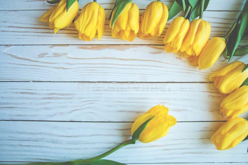 Tulipanes amarillos con las hojas verdes que ponen en la composición abstracta en un fondo de madera blanco imagen de archivo libre de regalías