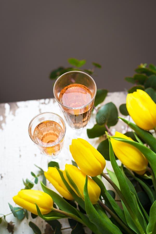 Tulipanes amarillos en una tabla blanca con un vidrio de vino rosado, primer imagen de archivo libre de regalías