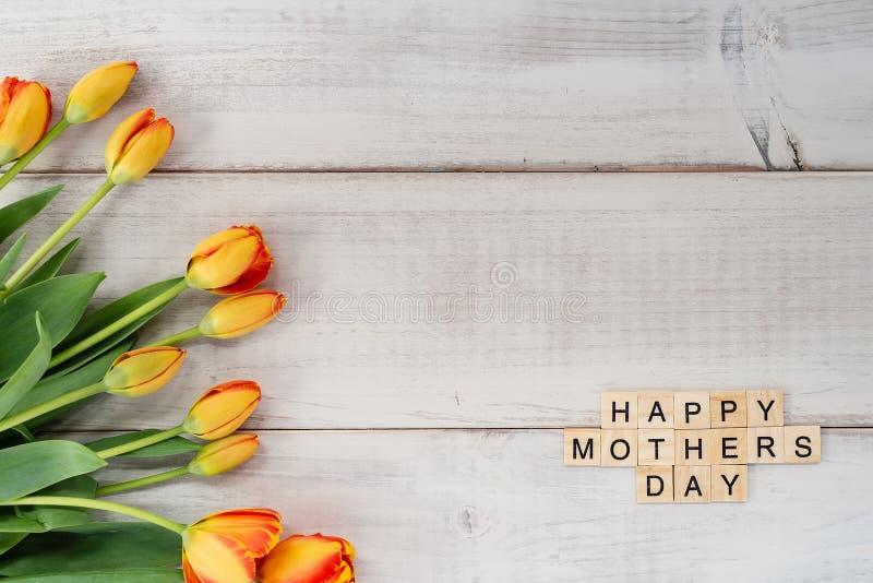 Tulipanes amarillos y rojos en la madera blanqueada con lío del día del ` s de la madre imagen de archivo libre de regalías