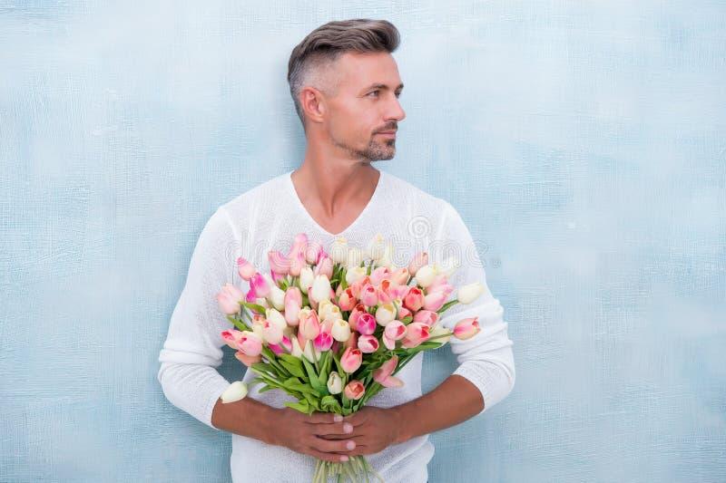 Tulipanes blandos para ella Para alguien especial Hombre con el ramo de los tulipanes Hombre hermoso que sostiene tulipanes rosad foto de archivo libre de regalías