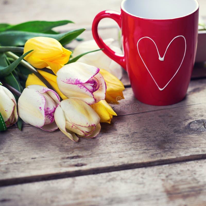 Tulipanes brillantes de la primavera y taza de café amarillos y blancos en vint imagen de archivo
