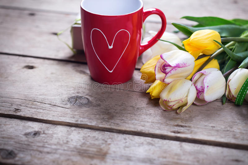 Tulipanes brillantes de la primavera y taza de café amarillos y blancos en vint foto de archivo libre de regalías