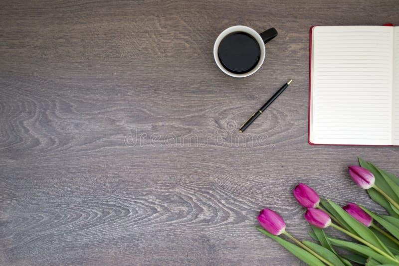 Tulipanes, café con el cuaderno fotografía de archivo libre de regalías