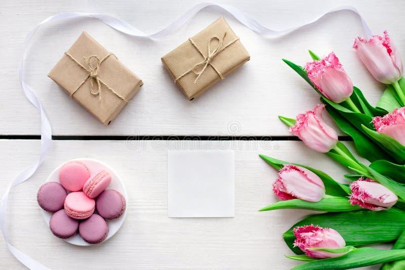 Tulipanes, cajas de regalo y fondo blanco de madera de los macarrones imagenes de archivo