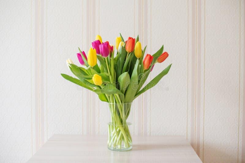Tulipanes coloridos grandes en un florero de cristal en la tabla en el fondo del papel pintado hermoso y apacible Amarillo, rojo  fotografía de archivo libre de regalías